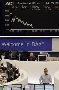Traders are pictured at their desks in front of the DAX board at the Frankfurt stock exchange September 24, 2012. REUTERS/Remote/Tobias Schwarz