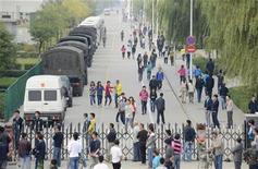 <p>Un grupo de trabajadores camina entre una serie de vehículos paramilitares policiales cerca de la entrada a una planta de Foxconn en Taiyuan, China, sep 24 2012. La taiwanesa Foxconn Technology cerró su planta de Taiyuan, en el norte de China, el lunes tras una disputa personal que derivó en una pelea en la que participaron 2.000 empleados en una residencia y que terminó con 40 heridos el domingo por la noche. REUTERS/Stringer</p>