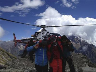 Rescue team members carry a tourist (C) after an avalanche at Mount Manaslu Base Camp September 23, 2012. REUTERS/Simrik Air/Handout