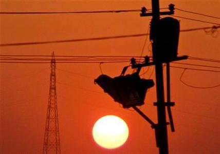 Sun sets behind street lights and electric pylons in Allahabad, February 5, 2006. REUTERS/Jitendra Prakash/Files
