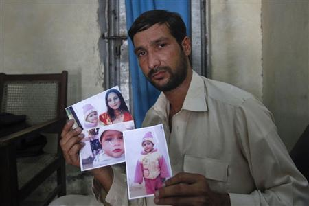 Muhummed Ihtisham, 30, a taxi driver, displays pictures of his wife and children during an interview with Reuters in Peshawar August 14, 2012. Provincial high courts are hearing more petitions but running up against congested legal machinery. Ihtisham petitioned the Peshawar High Court after his wife was tortured to death and their two toddlers thrown off a building in December but the case has been adjourned three times since because the paperwork was not ready. Picture taken on August 14, 2012. REUTERS/Fayaz Aziz