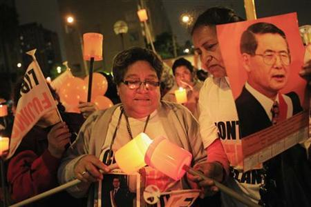 Supporters light candles while holding images of former President Alberto Fujimori during a vigil for his recovery outside San Felipe Clinic in Lima, September 21, 2012. Fujimori, who is in jail for human rights charges, was hospitalized on Wednesday after an 'hemorrhagic granuloma' was detected in the same area of the mouth where he was successfully operated several weeks ago, his son Kenji Fujimori said. REUTERS/Enrique Castro-Mendivil