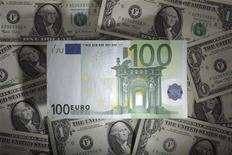 Банкнота в 100 евро лежит на долларовых купюрах в Варшаве, 13 января 2011 года. Курс евро стабилизировался на азиатских рынках после падения до недельного минимума к доллару на фоне опасений за финансовое положение Испании и слабых данных Германии. REUTERS/Kacper Pempel