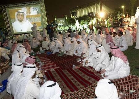 Kuwaiti protesters watch pro-opposition speakers on screens during a rally, in front of the Parliament building in Kuwait City September 24, 2012. REUTERS/Stephanie McGehee