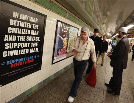 Cyrus McGoldrick, a member of the Council on American-Islamic Relations, talks to commuters as they walk by an advertisement that reads ''Support Israel/Defeat Jihad'' in the Times Square subway station in New York, September 24, 2012. REUTERS/Brendan Mcdermid