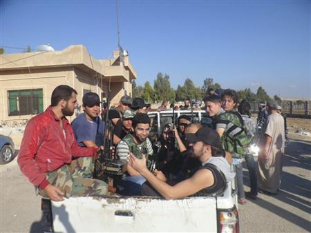 Members of the Jund Allah Brigades, part of the Free Syrian Army, sit in the back of a truck near Aleppo September 23, 2012. REUTERS/Shaam News Network/Handout