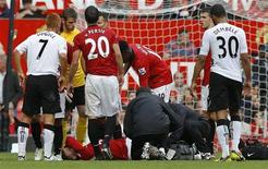 Wayne Rooney, do Manchester United, recebe tratamento após sofrer ferimento antes de ser retirado do campo durante partida contra o Fulham pelo campeonato inglês, em Old Trafford, Manchester.O atacante inglês que não joga há um mês por causa de um corte profundo sofrido na coxa contra o Fulham, deve retornar aos gramados nesta semana. 25/08/2012 REUTERS/Phil Noble