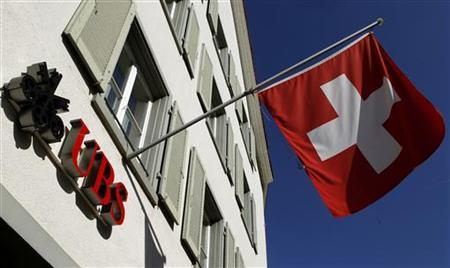 Switzerland's national flag is seen beside the logo of Swiss bank UBS in front of a branch office in the town of Riehen near Basel September 30, 2011. REUTERS/Arnd Wiegmann