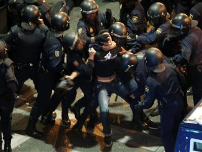 A demonstrator struggles with Spanish National Police riot officers outside the the Spanish parliament in Madrid September 25, 2012. Protesters clashed with police in Spain's capital on Tuesday as the government prepares a new round of unpopular austerity measures for the 2013 budget that will be announced on Thursday. REUTERS/Sergio Perez