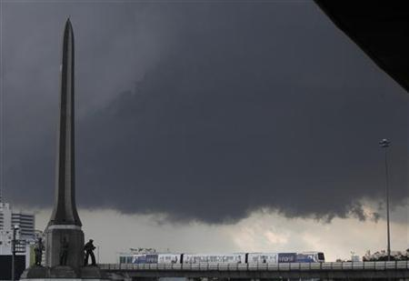 Rain clouds gather as a skytrain passes the victory monument in Bangkok September 25, 2012. REUTERS/Chaiwat Subprasom