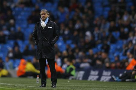 Manchester City's manager Roberto Mancini stands in the rain during their English League Cup soccer match against Aston Villa at The Etihad Stadium in Manchester, northern England, September 25, 2012. REUTERS/Phil Noble