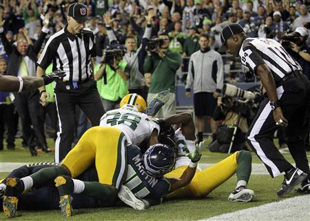 Referees wait to make the call on whether Seattle Seahawks wide receiver Golden Tate (bottom, obscured) caught the game winning touchdown against the Green Bay Packers in the fourth quarter of their NFL football game in Seattle, Washington, September 24, 2012. REUTERS/Anthony Bolante