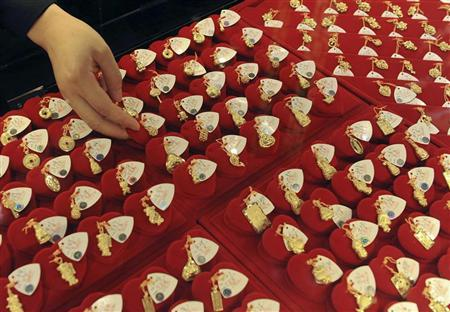 A vendor arranges gold accessories at a jewellery shop in Hefei, Anhui province May 11, 2010. REUTERS/Stringer