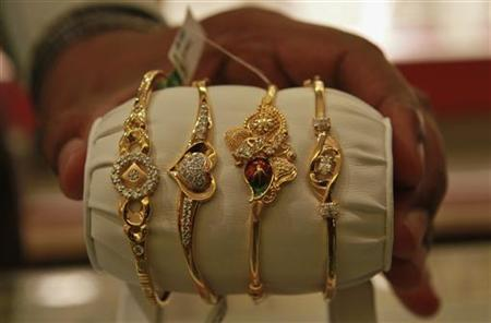 The salesman displays gold bangles to a customer at a jewellery showroom in Chennai March 23, 2012. REUTERS/Babu/Files