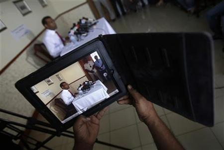 A journalist films with his iPad as Maldives' former President Mohamed Nasheed addresses a news conference in Male August 31, 2012. REUTERS/Adnan Abidi