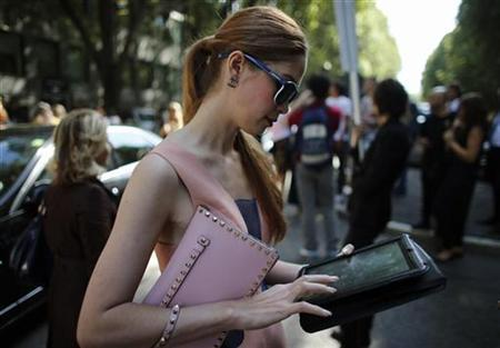 A woman looks at her iPad tablet at Milan Fashion Week September 20, 2012. REUTERS/Stefano Rellandini