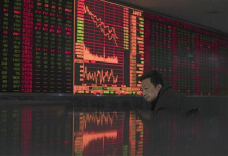 An investor sits in front of an electronic board showing stock information at a brokerage house in Wuhan, Hubei province January 4, 2012. REUTERS/Stringer/Files