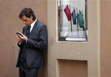 A man looks at his iPhone in Rome September 11, 2012. Italy has long been an Internet laggard, its creaky networks stunting the development of online commerce and banking. Italians pay among the highest prices in Europe for broadband speeds on a par with Estonia or Cyprus. As a result, only half the population uses the Internet at least once a week and Italian firms generate 5.4 percent of sales on-line compared to 13.9 percent elsewhere in Europe. Now the reformist government of Prime Minister Mario Monti has identified better broadband as a national priority to spur growth and reduce Italy's 11 percent unemployment and bulging deficits. REUTERS/Max Rossi