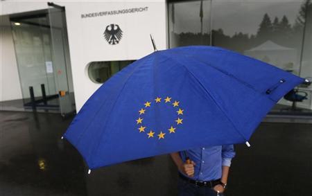 A person with an umbrella featuring the symbol of the European Union walks towards the interim facility of Germany's high constitutional court ( Bundesverfassungsgericht ) during heavy rainfall in Karlsruhe, September 11, 2012. REUTERS/Kai Pfaffenbach
