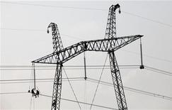 Рабочие ремонтируют линии электропередачи около деревни Соленоозерное в Хакасии, 1 июля 2012 года. Российский электросетевой госоператор Холдинг МРСК уронил прибыль на 40 процентов в первом полугодии на фоне низких тарифов, замороженных властями в борьбе с инфляцией накануне выборов. REUTERS/Ilya Naymushin
