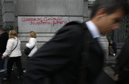A woman asks for money next to a graffiti that reads, ''We want to build our future'' outside the headquarters of the Bank of Spain in central Madrid September 26, 2012. REUTERS/Susana Vera