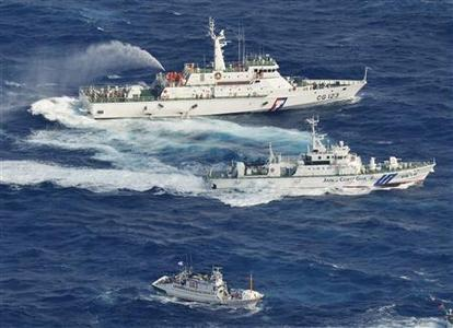 An aerial view shows Japan Coast Guard patrol ship (C) and Taiwan's Coast Guard vessel (top) spraying water at each other near the disputed islands in the East China Sea, known as Senkaku in Japan, Diaoyu in China and Tiaoyutai in Taiwan, in this photo taken by Kyodo September 25, 2012. A group of fishermen from Taiwan said as many as 100 boats escorted by 10 Taiwan Coast Guard vessels would arrive in the area later on Monday. Mandatory Credit. REUTERS/Kyodo