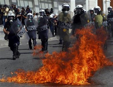 A molotov cocktail explodes beside riot police officers near Syntagma square during a 24-hour labour strike in Athens September 26, 2012. REUTERS-Yannis Behrakis