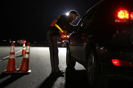 A Jefferson County Sheriff Deputy asks a driver if he has been drinking while smelling for alcohol at a mobile Driving Under the Influence (DUI) checkpoint in Golden, Colorado late April 12, 2008. REUTERS/Rick Wilking