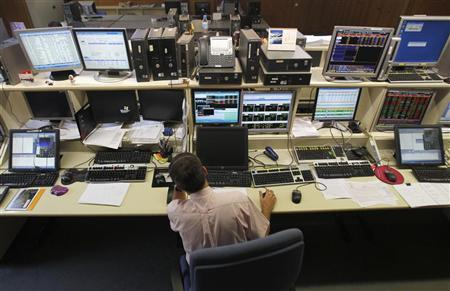 A trader looks at computer screens during Spain's bonds auction in a broker's office in Barcelona June 21, 2012. REUTERS/Albert Gea
