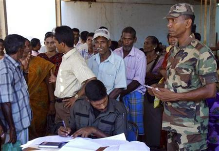 Army soldiers take down the details of families as they return to their homes, after they were released from Manik Farm Internally Displaced Persons (IDP) camp near Vavuniya, 254 km (158 miles) north of Colombo, May 13, 2010. REUTERS/Stringer/Files