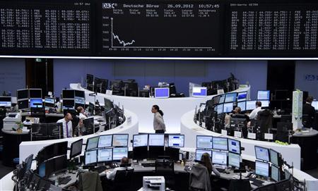 Traders are pictured at their desks in front of the DAX board at the Frankfurt stock exchange September 26, 2012. REUTERS/Remote/Marte Kiessling