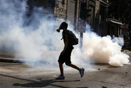 A masked protester runs through a cloud of tear gas in Athens' Syntagma square during a 24-hour labour strike September 26, 2012. REUTERS-Yannis Behrakis