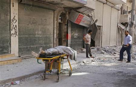The body of a dead civilian lies on a stretcher on a street after an air-strike in Aleppo's al-Shaar district September 23, 2012. REUTERS/Zain Karam