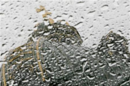 The Swiss Parliament building is seen trough raindrops on a glass roof on the Swiss Federal square in Bern September 12, 2012. REUTERS/Pascal Lauener