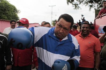 Venezuela's President Hugo Chavez poses usingboxing gloves during a campaign rally in Acarigua in the state of Portuguesa September 24, 2012. REUTERS/Miraflores Palace/Handout