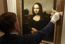 """Historiador de arte e membro da Fundação Mona Lisa, Stanley Feldman, limpa o vidro de proteção de quadro em Genebra, na Suíça. Uma versão mais nova da """"Mona Lisa"""", de Leonardo da Vinci, será apresentada na quinta-feira, com a sugestão de que ela é a versão original daquela que é considerada a pintura mais famosa do mundo. 26/09/2012 REUTERS/Denis Balibouse"""