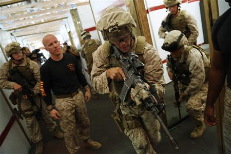 U.S. Marines work with instructors on a building-clearing drill as they train to be members of a Fleet Antiterrorism Security Team (FAST) unit at a training ground in Chesapeake, Virginia, September 25, 2012. Marine Corps officials say the intense training done at this site is imperative to ensure the young Marines will be ready to respond to threats against U.S. facilities on a moment's notice. But, they say, looming budget cuts may threaten the pace and realism of the training. The men who serve in the Marine Corps Fleet Anti-terrorism Security Teams (FAST) sign up for an extra, fifth year of service to get a spot on the high-speed force, then spend nearly four weeks of 10-hour days training at this Cold War-era Navy listening station. Picture taken September 25, 2012. REUTERS/Jonathan Ernst