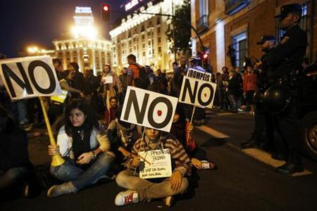 Protesters take part in a sit-in during a demonstration outside Madrid's Parliament September 26, 2012. REUTERS/Susana Vera