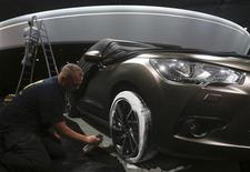 A worker prepares a car for display at the Citroen exhibition area on the eve of a media preview at the upcoming Paris Car Show September 26, 2012. REUTERS/Jacky Naegelen