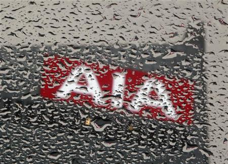 An AIA logo, seen through a footbridge filled with rain drops, is displayed on top of AIA Central in Hong Kong February 24, 2012. REUTERS/Bobby Yip