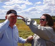 Australia's richest woman and mining magnate, Gina Rinehart (R), adjusts a cap on the head of Australia's Minister for Resources, Energy and Tourism, Martin Ferguson during a visit to the Alpha Coal project test pit in the Galilee Basin about 800kms (497 miles) northwest of Brisbane in this November 6, 2010 handout picture. REUTERS/Queensland Resources Council/Handout