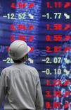 Мужчина изучает табло с биржевыми индикаторами в Токио 17 апреля 2009 года. Азиатские фондовые рынки выросли благодаря ралли китайских акций. REUTERS/Toru Hanai