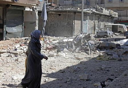 A woman walks on rubble as she crosses a street after checking her damaged house in in Aleppo's district of Bustan Al-Basha September 26, 2012. REUTERS/Zain Karam