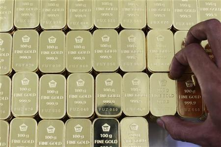 Gold pieces, each weighing 100 grams, are seen arranged at the state-owned mining company PT Antam Tbk metal refinery in Jakarta July 13, 2012. REUTERS/Beawiharta