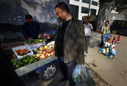 Dissident Chinese artist Ai Weiwei (C) buys fruit from a local vendor on the street outside the Chaoyang District Court before trying to attend his appeal verdict hearing in Beijing September 27, 2012. REUTERS/David Gray