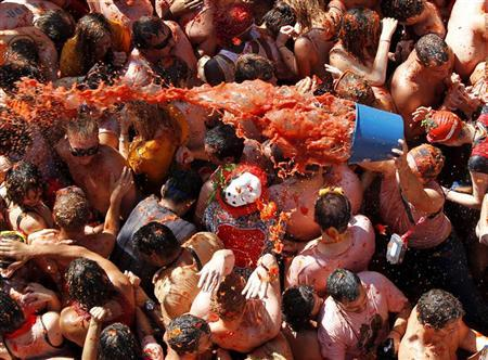 A reveller pours tomato pulp with a bucket into the crowd during the annual ''Tomatina'' (tomato fight) in the Mediterranean village of Bunol, near Valencia August 29, 2012. REUTERS/Heino Kalis