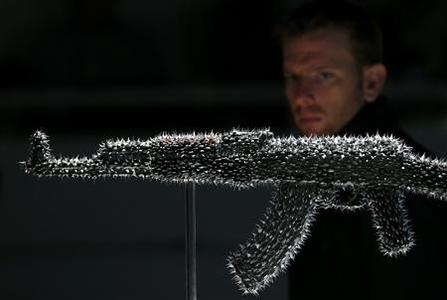 A visitor looks at Nancy Fouts's ''Don't Touch'', at the AKA Peace exhibition at the Institute for Contemporary Art (ICA) in central London September 26, 2012. Bran Symondson, a former soldier, conceived the AKA Peace project, in which artists turn decommissioned AK47 assault rifles into works of art. REUTERS/Andrew Winning
