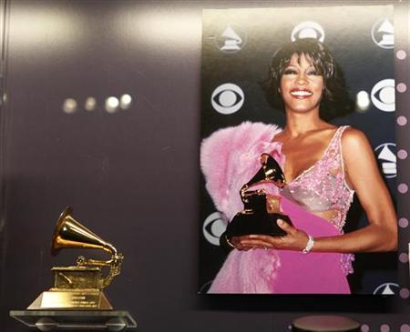 A photograph of the late singer Whitney Houston holding a Grammy Award is displayed next to one of her Grammys during a press preview of the new exhibit ''Whitney! Celebrating The Musical Legacy of Whitney Houston'', at The Grammy Museum in Los Angeles, California August 15, 2012.REUTERS/Fred Prouser