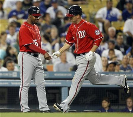 Former Washington Nationals third base coach Bo Porter (16) congratulates Adam LaRoche rounding third hitting a solo home run against the Los Angeles Dodgers during the seventh inning of their MLB National League baseball game in Los Angeles, California April 28, 2012. REUTERS/Alex Gallardo