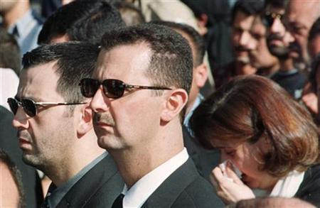 File photo of Bashar al-Assad (C), his younger brother Maher (L) and sister Bushra walking behind the coffin of their father the late Syrian President Hafez al-Assad at the start of the state funeral in Damascus June 13. REUTERS/Stringer/Files